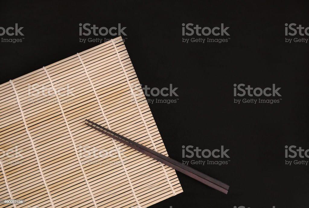 Chopsticks on bamboo matt stock photo