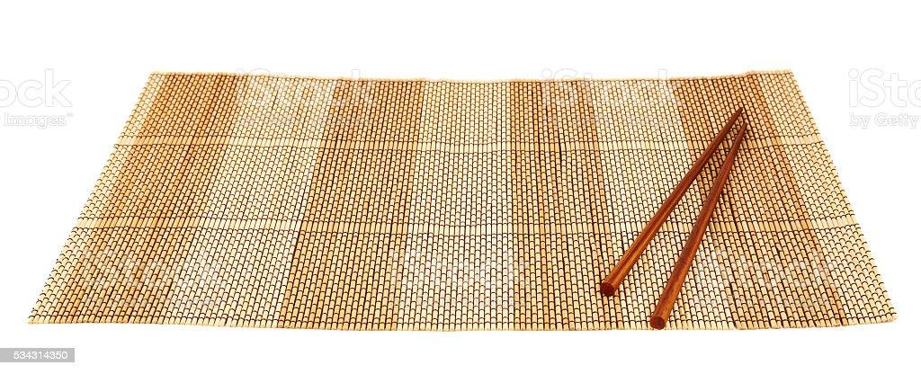 Chopsticks over a bamboo mat stock photo