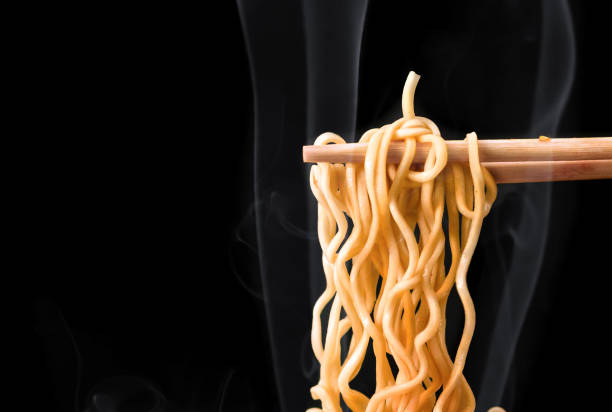 箸は、暗い背景に煙でおいしい麺を拾います。 - ラーメン ストックフォトと画像