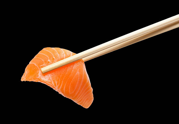 Chopsticks with sliced raw salmon stock photo