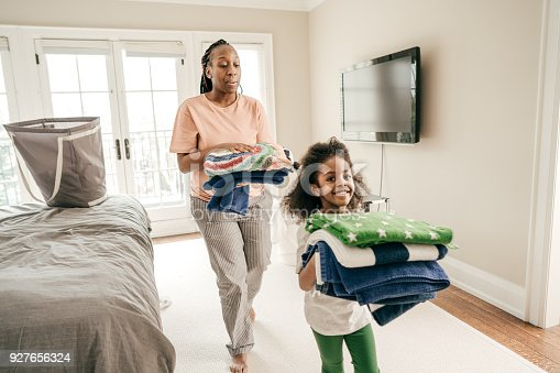Daughter and mother folding clean towels
