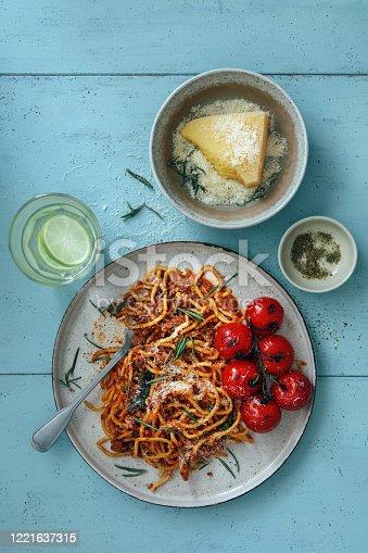 Chorizo Creamy Tomato Pasta. Flat lay top-down composition on blue background.