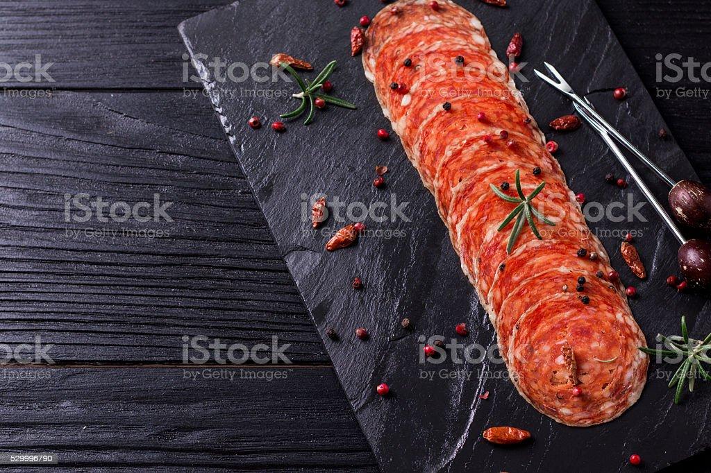 Chorizo salami sausage on rustic background. stock photo