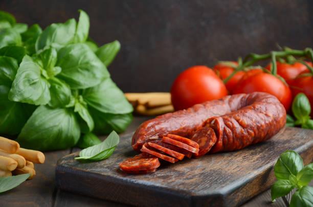chorizo-wurst. traditionelle spanische chorizo-wurst mit frischen kräutern und tomaten. - chorizo wurst stock-fotos und bilder