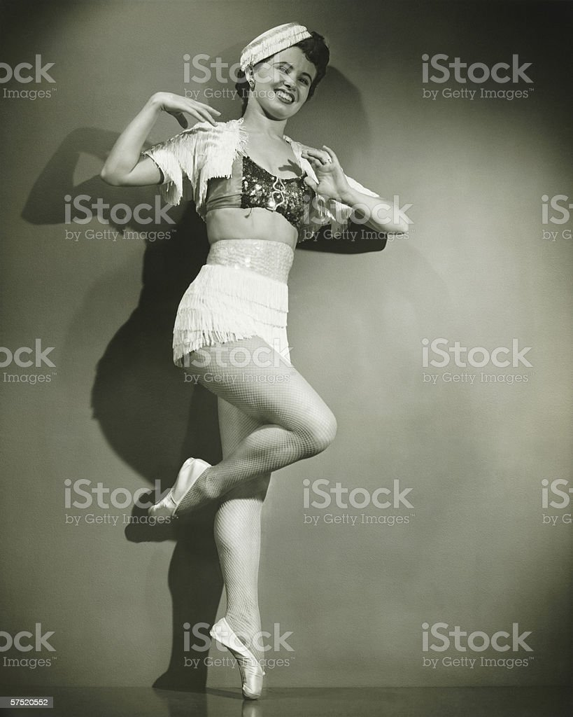 Chorus girl dancing in studio, (B&W) stock photo
