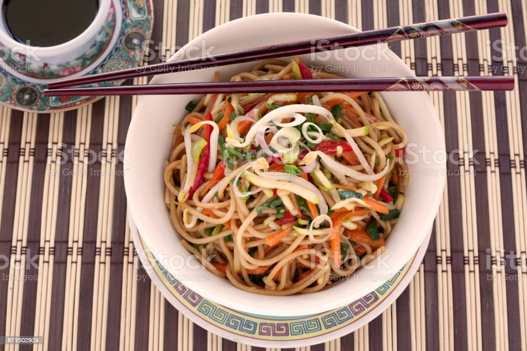 Chow mein in bowl with chopsticks and soy sauce stock photo