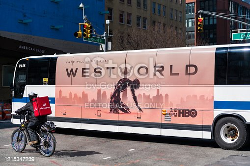 New York City, USA - March 19, 2020: During a state of emergency is New York City due to the growing coronavirus pandemic, a food delivery person for Chowbus rides his bike adjacent to a New York City bus advertising the latest season of HBO's science fiction series Westworld.
