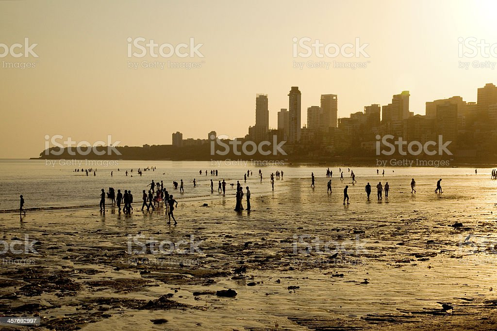 Chowpatty Beach at sunset, Mumbai, India. Chowpatty Beach at sunset, Mumbai, India. Silhouettes of people walking along the beach & enjoying the sunset, with skyscrapers in the background. Asia Stock Photo
