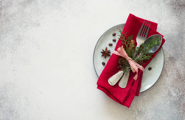 chrismas table place setting. tableware with evergreen twigs, cone and spice - evergreen plant stock photos and pictures
