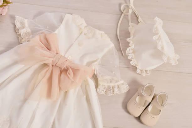 bautizo vestido de bebé. Primer plano de un lindo vestido de bebé recién nacido. Elegante vestido blanco bordado. Concepto de educación y moda infantil - foto de stock