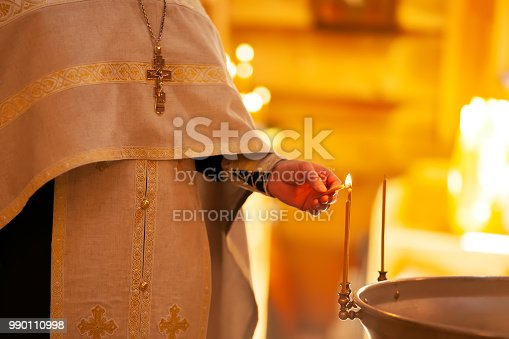 Christening ceremony in the Orthodox church, priest lighting candles at children baptismal font, close-up.