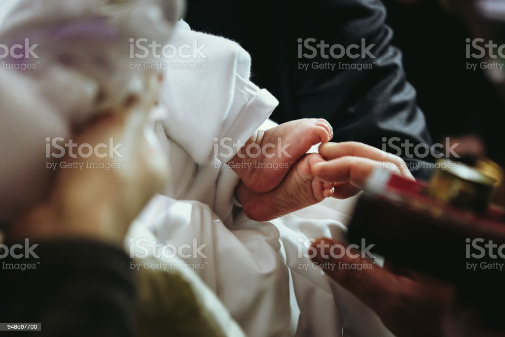 christening of little baby in church, close-up feet and priest hand stock photo