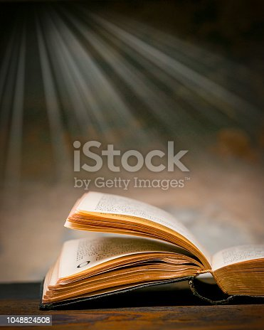 Open Christian bible with light rays streaming downward in background