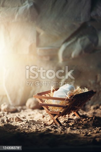 Christian Christmas concept. Birth of Jesus Christ. Wooden manger in cave background. Banner, copy space. Nativity scene symbol. Jesus is reason for season. Salvation, Messiah, Emmanuel, God with us, hope.