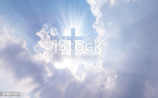 istock Christian cross appears bright in the sky 879917312