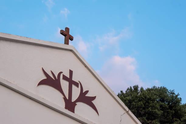 christliches kreuz hängt an der wand einer kapelle. - achtsamkeit persönlichkeitseigenschaft stock-fotos und bilder