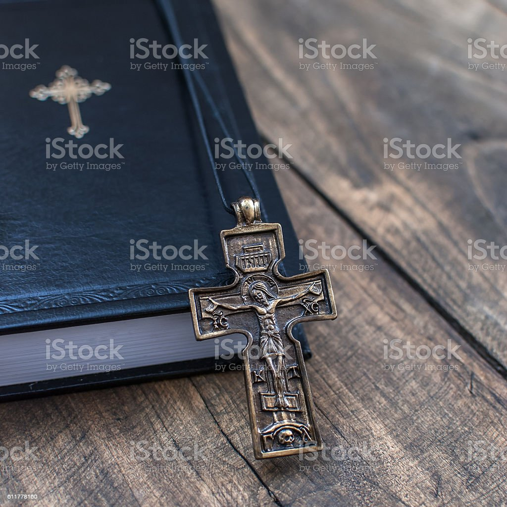 Christian cross necklace next to holy Bible stock photo
