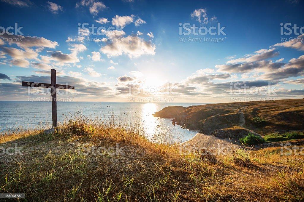 Christian cross on a wild beach with a wonderful sunrise stock photo