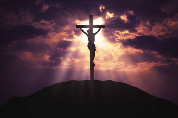 Christian cross on hill at sunrise