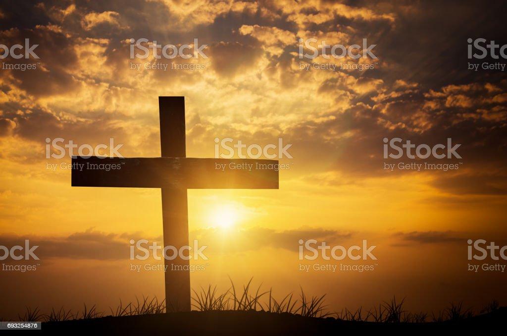 christian cross on sunset background stock photo