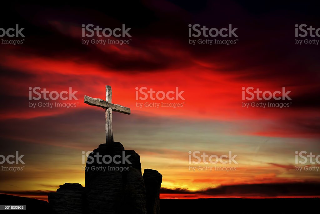 Christian cross over dark red sunset background stock photo
