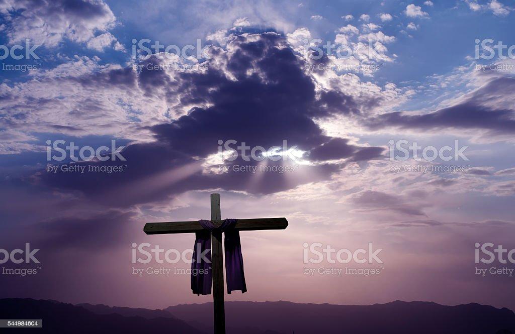 Christian cross over dark sunset background stock photo