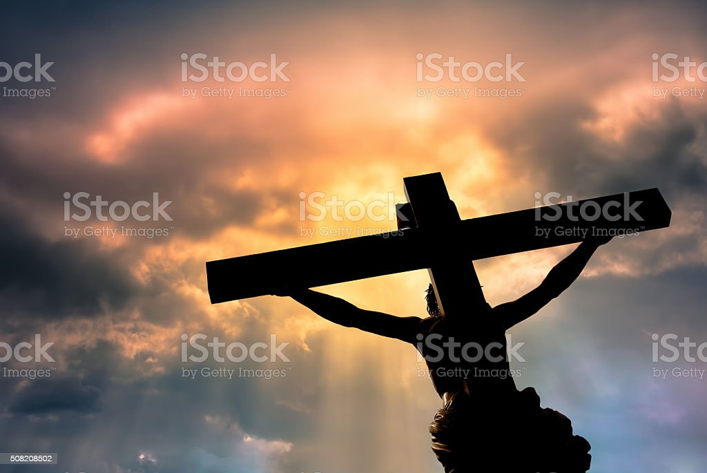 Christian cross with Jesus Christ statue over stormy clouds stock photo
