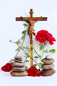 A Christian cross with red roses, ivy and stone towers
