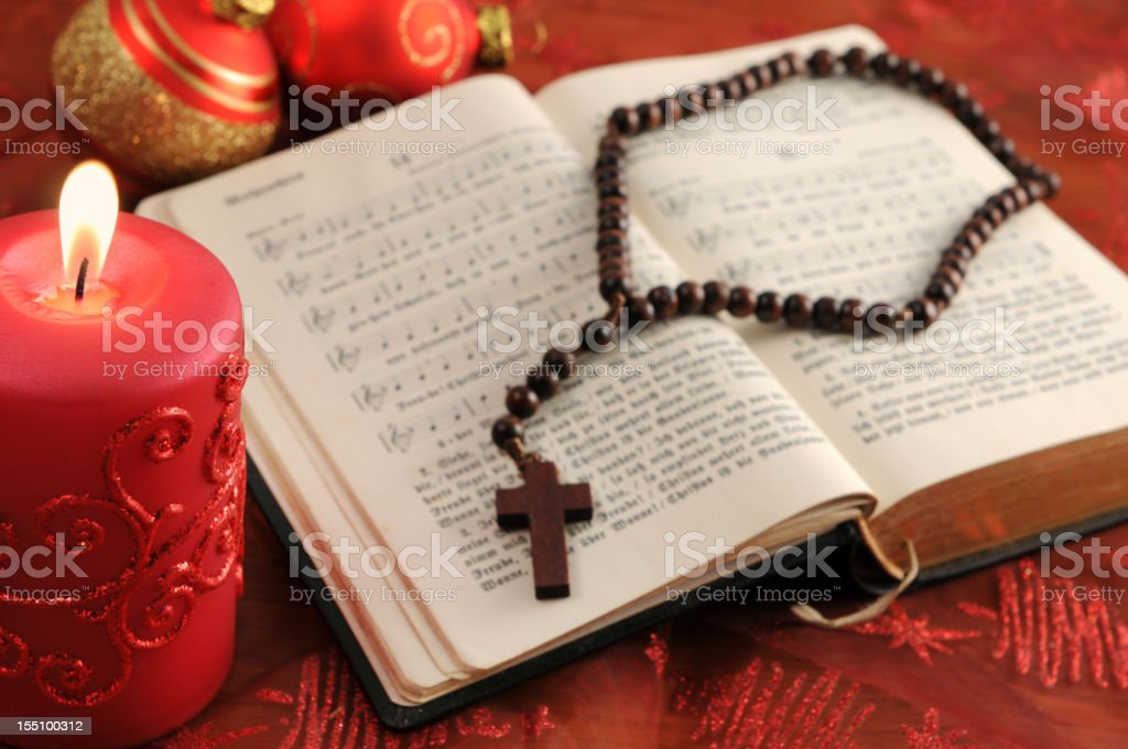 christian hymnal book with red candle rosary bead Xmas balls stock photo
