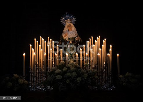 carved image of Virgin, isolated with black background surrounded by lit candles