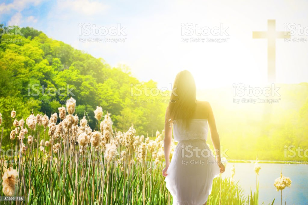 Christian Near Death Experience A woman gazes upon a cross in a field with bright light surrounding it. Adult Stock Photo