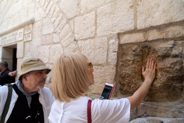 Christian pilgrims visiting Via Dolorosa in Jerusalem Jerusalem, Israel - June 15, 2018: Christian pilgrims visiting the 5th station of Via Dolorosa in Jerusalem, Israel. historical palestine stock pictures, royalty-free photos & images