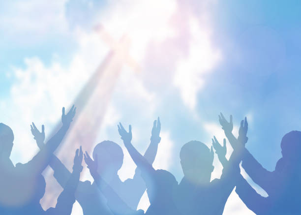 Christian Praise and Worship soft focus of Christian people group raise hands up worship God Jesus Christ together in church revival meeting with an image of wooden cross over cloudy sky can be used for Christian worship background revival stock pictures, royalty-free photos & images