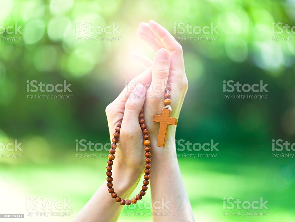 christian prayer beads in the hand of woman stock photo