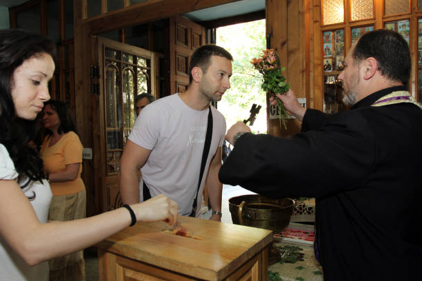 Christian priest gives people to kiss the cross and blesses them with holy water on a big church holiday in Sofia, Bulgaria on may 6, 2012. stock photo