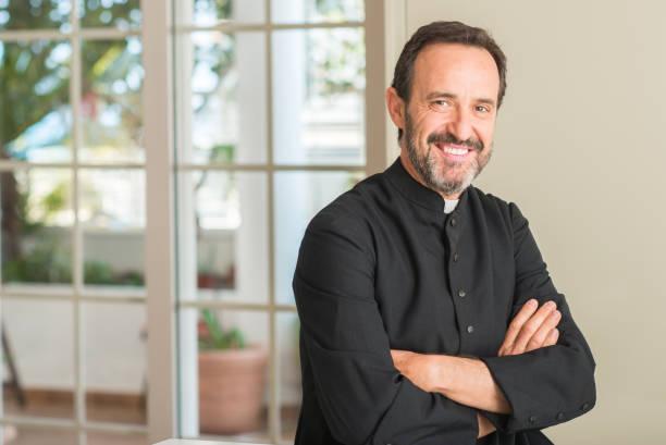 homem de sacerdote cristão com um sorriso no rosto de pé e sorrindo com um sorriso confiante, mostrando os dentes - padre - fotografias e filmes do acervo