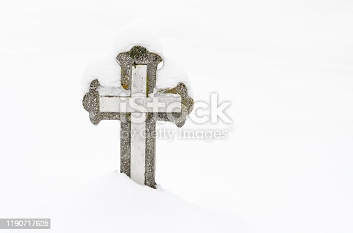 istock Christian stone cross in the cemetery, covered with snow . 1190717625