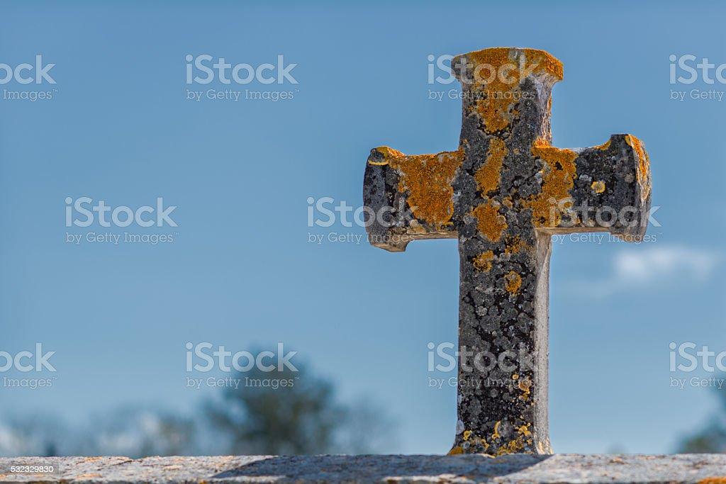 christian stone cross with lichen in the sun stock photo