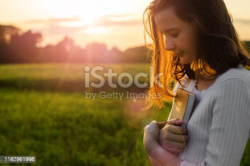 Christian teenage girl holds bible in her hands. Reading the Holy Bible in a field during beautiful sunset. Concept for faith, spirituality and religion. Peace, hope
