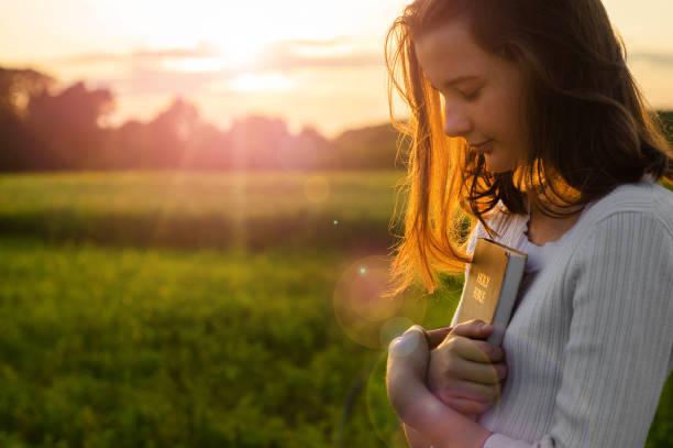 chrześcijańska nastolatka trzyma biblię w rękach. czytanie biblii świętej w polu podczas pięknego zachodu słońca. koncepcja wiary, duchowości i religii - bóg zdjęcia i obrazy z banku zdjęć