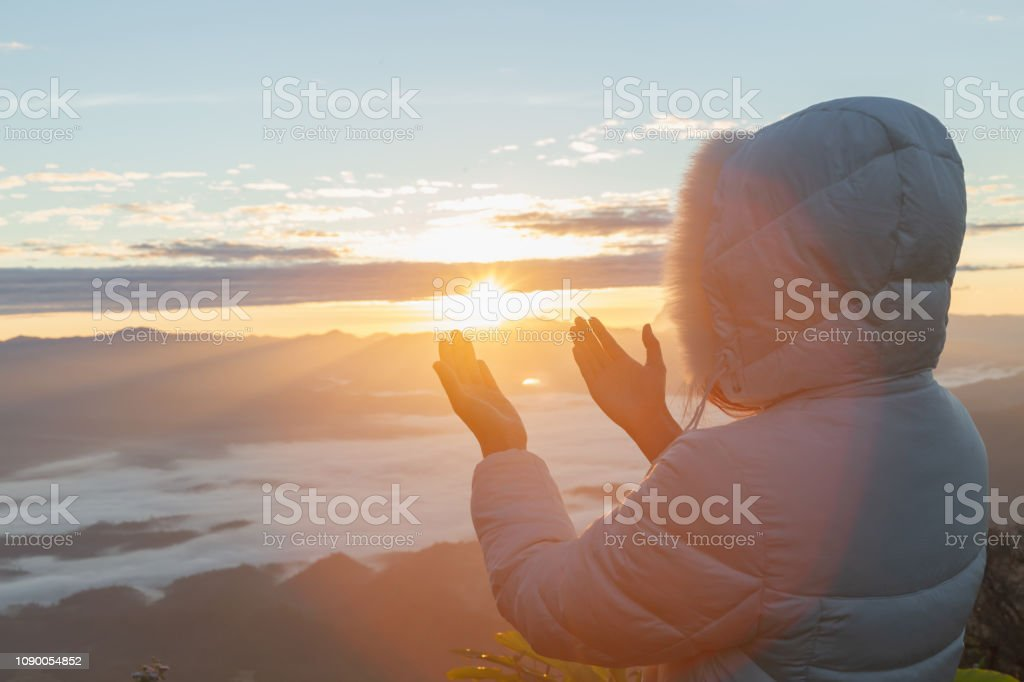 Christian woman hands praying to god on the mountain background with...