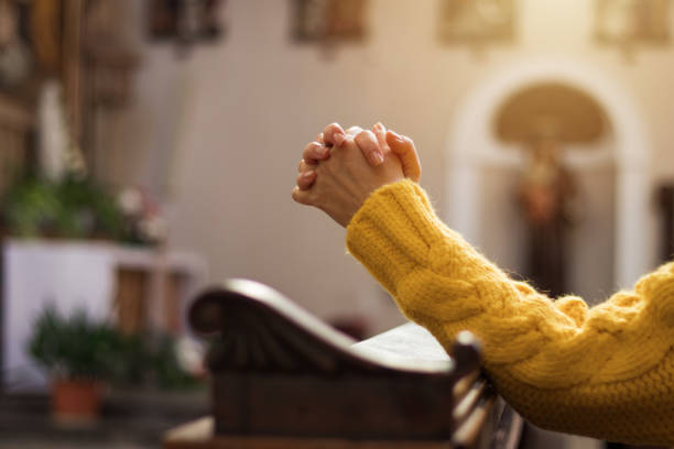Christian woman is praying with hands crossed in church. Christianity and religious symbol. Belief in Jesus Christ pew stock pictures, royalty-free photos & images