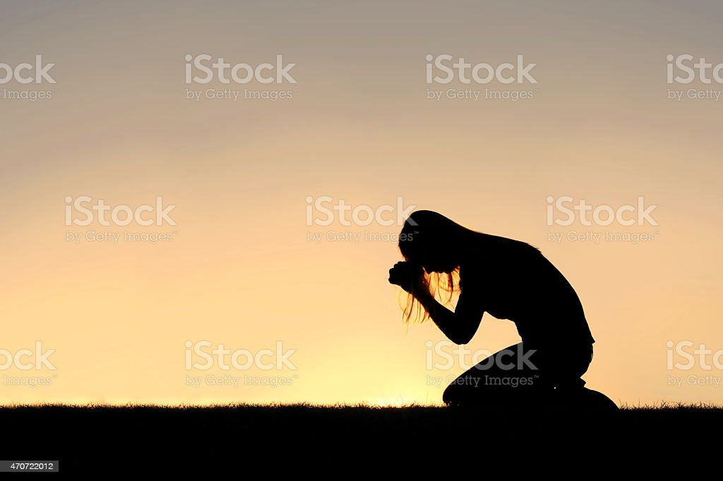 A silhouette of a young Christian woman is bowing her head in prayer,...