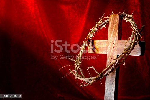 Christianity, Resurrection of Jesus Christ and Christian holiday of Easter concept with a bright beam of light shining on a cross and a crown of thorns with drops of the savior blood with copy space