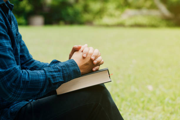 Christians and Bible study concept.Young man sitting and prayer on bible.copy space