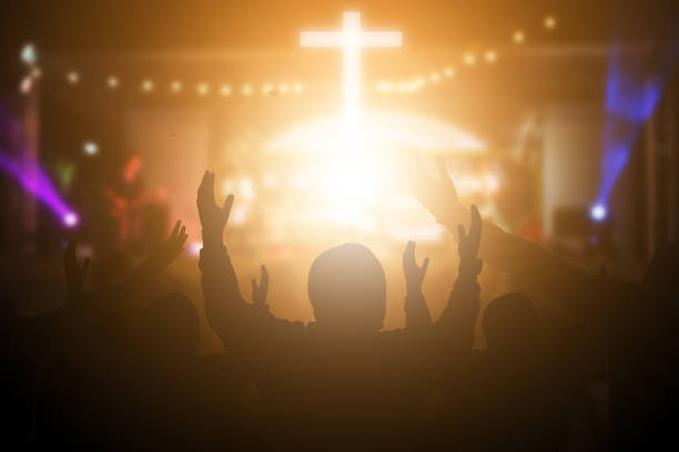christians raising their hands in praise and worship at a night music concert. eucharist therapy bless god helping repent catholic easter lent mind pray. christian concept background. - church stock photos and pictures