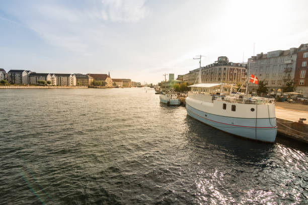 Christianshavn neighborhood canal with boats moored at sunset in the city of Copenhagen stock photo