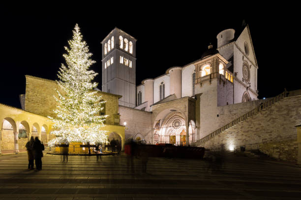 Christmas 2017 in Assisi (Umbria), with a view of San Francesco Christmas 2017 in Assisi (Umbria), with a view of San Francesco papal church at night, with big lighted tree and people on the square umbria stock pictures, royalty-free photos & images