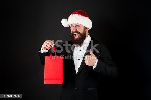 Christmas advertising. Happy manager give thumb up to shopping bag. Advertising holiday gift. Holiday advertising. Advertisement. Festive promotion and marketing. Advertising product, copy space.