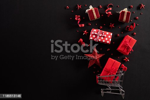 Christmas and Boxing Day background concept. Top view of shopping cart splash out Christmas decoration with gift box red star berries and ribbon on black background.